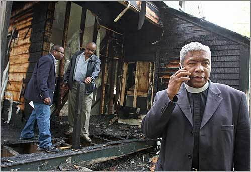 Rev. Eugene F. Rivers 3d spoke on a phone while surveying the damage to the Ella J. Baker House in Dorchester. The building, which houses a program led by Rivers to help at-risk youth, was the site of a suspected arson attack.