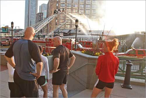 Morning joggers stopped to look at the remaining firefighting efforts on the Boston waterfront this morning.