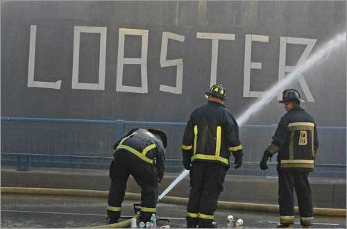 Firefighters adjusted the ground line near a 'Lobster' sign. The flames spread so fast that firefighters had to call for reinforcements when they began quelling the blaze.