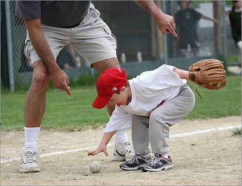 Justin went after the ball as his Challenger Little League coach, Dave Pontes of Billerica, encouraged him during the game.