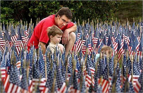 Mathew Riley and his children, Aidan, 3, and Lila (right), 1, paused at the Field of Flags, which was planted in the Main Street front yard of the First Baptist Church of Holden. Each flag represents a soldier killed in Afghanistan and Iraq.