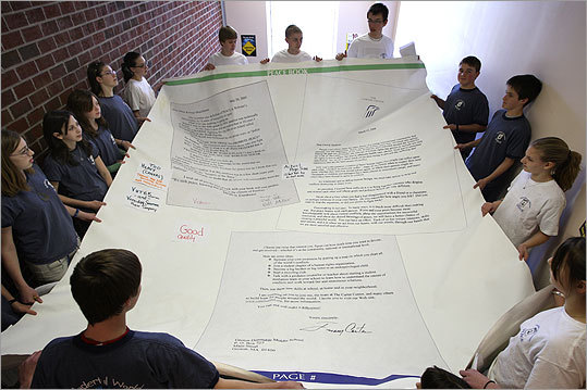 Groton-Dunstable Regional Middle School club members hold a prototype of a page from what they hope will become a record-setting book.