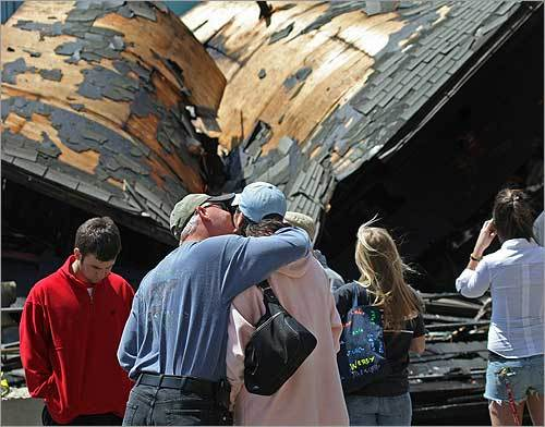Alan Anderson gave his wife, Kathy, a kiss and a hug in front of what's left of James Hook & Co. after Friday morning's fire. The seven-alarm fire broke out around 3:30 a.m. on the Boston waterfront by the Fort Point Channel. No one was reported injured, and there was no indication of how the fire started.