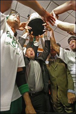 Celtics players gathered around the Eastern Conference trophy.