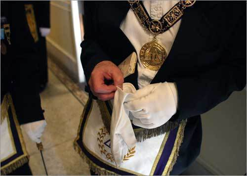 "Since hands can offer clues about a person's station in life (i.e. calloused and rough on a craftsman), Masons wear gloves as a symbolic gesture of unity and equality. There are, however, levels of membership within the organization, known as ""degrees."" How members attain a higher rank and the rituals associated with conferring those degrees remain shrouded in mystery. Members take an vow of silence. Additionally, ""members cannot talk about the 'modes and methods of recognition'...certain signs that can be used to recognize one mason from another,"" said Robert Huke, a spokesman for the Massachusetts Grand Lodge. (Left) Rev. John R.S. Higgins, Grand Chaplain of the Massachusetts Grand Lodge."