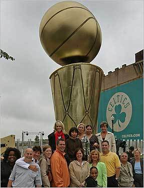 Employees of the Division of Professional Licensure of Massachusetts pose in front of a replica of the Larry O'Brien championship trophy during their break near the TD Northbank Garden.