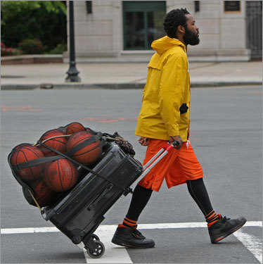 Rashaun Daniels, a street performing juggler, makes his way toward Causeway Street and the TD Northbank Garden for Game 1 of the NBA Finals.
