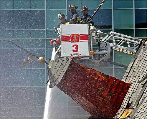 Boston firefighters hosed down a section of the James Hook Lobster Company. The downtown Boston landmark was destroyed by the blaze.