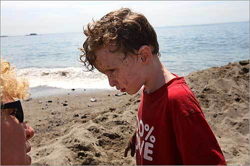 Letitia Proulx pleaded with her son Theo, 4, to rinse his sandy face in the water at Devereux Beach Tuesday morning. The family was visiting Marblehead from Britain.
