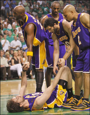 Los Angeles Lakers teammates help Pau Gasol (16) from the floor in the second quarter.