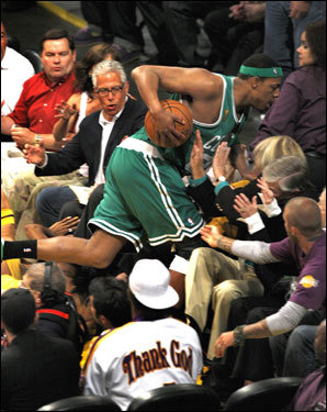 Paul Pierce bounded into the crowd, in front of David Beckham (right), after chasing down an errant pass in the first quarter.