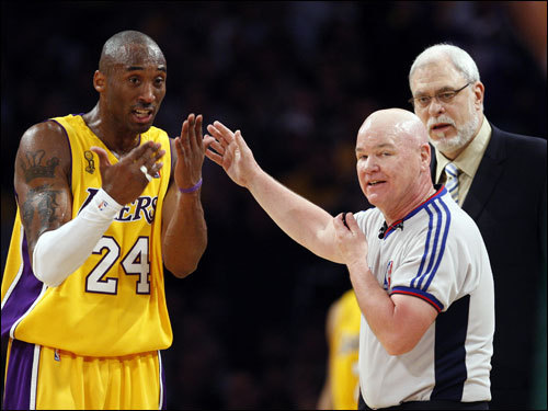 Lakers guard Kobe Bryant (24) and referee Joe Crawford (center) talked during the game as Laker coach Phil Jackson (right) looked on.