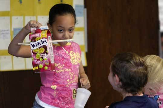 Barbieri Elementary second-grader Adriana Carrasquillo, 8, demonstrates alternative versions of a wind turbine created as part of a Museum of Science engineering curriculum at the Framingham school.