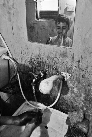 Palestinian mechanic Jihad Robin, 12, washes his hands and face, at the car garage where he works in Ramallah.