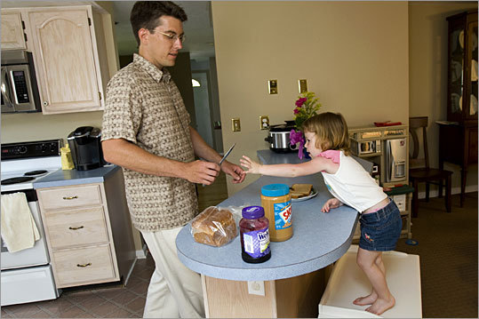 Dan Boucher makes a sandwich for his 4-year-old daughter, Lauren, at home in Worcester. Boucher says he's happy as a stay-at-home dad.