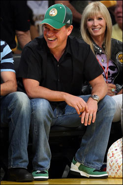 Actor Matt Damon satcourt side in a Celtics hat during the game.
