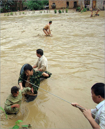 Rescuers evacuated residents trapped in their homes by rising flood water in Wangmo town, southwest China's Guizhou province, on June 16, 2008. Heavy rains in China have left at least 65 people dead and missing across nine provinces over the past 10 days, with more than 1.27 million people evacuated in the hardest-hit areas, with large swathes of farmland submerged and economic losses already totaling more than 10 billion yuan ($1.4 billion).