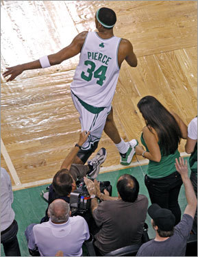 A cameraman (left) used Paul Pierce (34) to steady himself during the game.