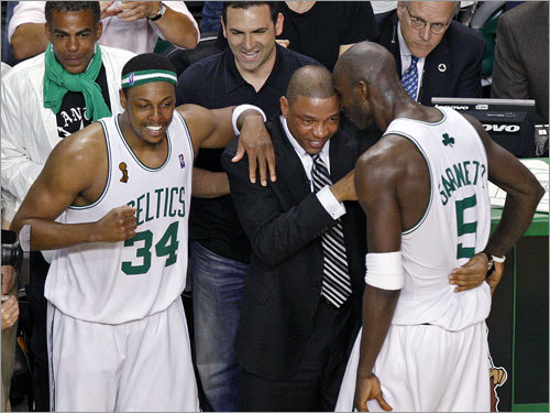 Paul Pierce (left), Doc Rivers (center), and Kevin Garnett (right) celebrated on the sidelines.