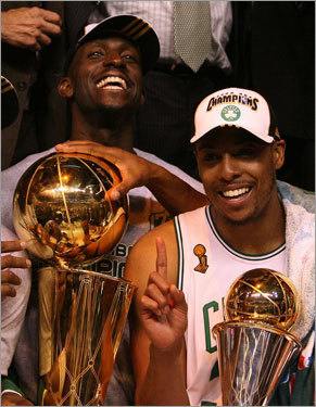 Kevin Garnett and Paul Pierce, respectively, hoist the Larry O'Brien and NBA Finals MVP trophies.