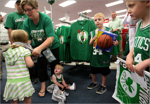 Kimberly Dube helps her 3-year-old daughter Katherine try on a Celtics shirt at Modell's Sporting Goods as Katherine's brothers Zachary, Joshua and Noah watch.
