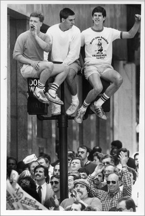 Celts fans Mike Bishop (left), Tom Leahy (center) and Brian Purcell (right) sat on pedestrian traffic signals on Tremont St. and Court St. near City Hall during the 1986 Celtics Championship Parade.