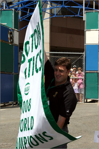Celtics owner Wyc Grousbeck unfurls the 2008 championship banner for fans before boarding a duck boat.