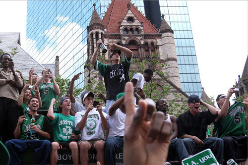 Celtics fans sat on top of a bus stop on Boylston Street near Copley Square to get a better seat for the parade.