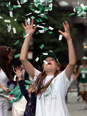 Molly Crumby, 10, of Stoughton, played with confetti on Cambridge Street after the Celtics rolling rally passed the location that she had been watching from on Boylston Street.