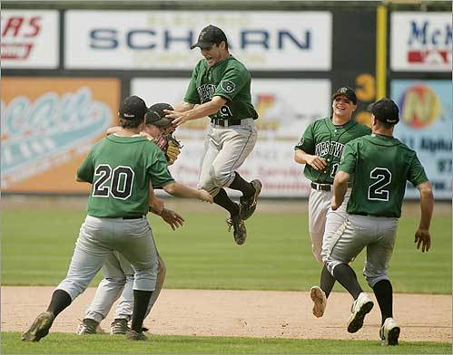 Westwood players surrounded the starting pitcher, John Sheehan, who leaped into the air after Westwood defeated Frontier 12-6 during the Division 3 State Championship Baseball Game at LeLacheur Park in Lowell.