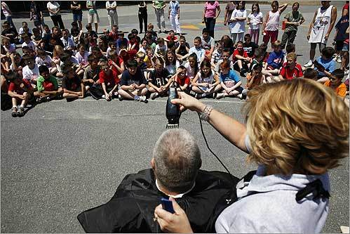 George Paul, principal of the Louise Davy Trahan School, had his head shaved by Lorri McAteer, a hairdresser and parent of a student at the school in Tewksbury. Paul agreed to shave his head if the school was able to raise over $3,000 for the Children's Hospital, where one of the school's students Lia DiFronzo, 8, is being treated for leukemia.