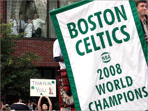 Boston Celtics owner Wyc Grossbeck (visible in the top right corner) held the world championship banner as the Celtics rolling rally passed the Four Seasons Hotel on Boylston Street.