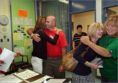 Angela Cristiani (left), a school psychologist at Grover Cleveland School, hugged special education teacher Keith Guyette. Assistant principal Marybeth Bernard (center) stood by as Anne Sweeney, who is retiring after 28 years, was embraced by school secretary Donna Bolles. The Dorchester school closed this week after 80 years.