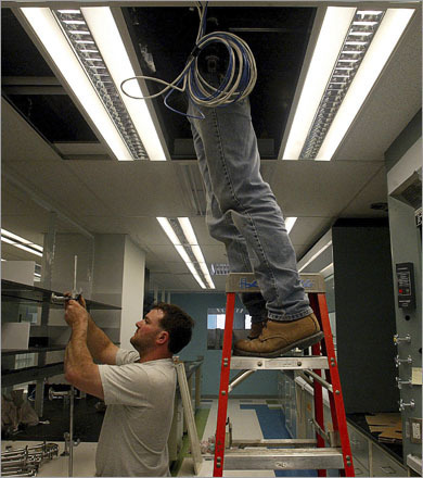 Buy photographs by Pat Greenhouse Carpenter Jason Giancaterino, left, assembles distillation racks for fumehoods while electrician Marc Mericantante installs controls for ventilation in a Perini Building Company construction in Cambridge in 2003.