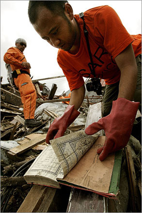 In Banda Aceh two weeks after the tsunami, a member of the Tatlelolco Azteca International Rescue Brigade, aka Los Topos (the moles), from Mexico City looks for a page to tear from a holy Koran to be placed on top of the bodies they find. A Muslim prayer will be said before zipping the body bag. The team leader Hector 'Chino' Mendez watches him. His team of 12 is made up from volunteers and all of their equipment and attire is donated.
