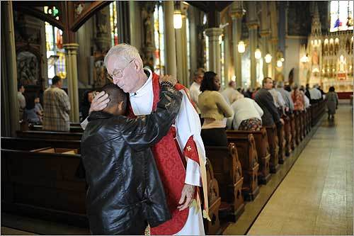 Father Frederick W. O'Brien received greetings from Noel O'Laoghaire, 19, during the last procession of the Latin Mass at Holy Trinity Church in Boston, which is being closed.