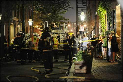 Boston firefighters, including a hazardous materials team, stood in front of 21 Temple Street where a chemical spill took place July 1 in an apartment in the Beacon Hill area of Boston.