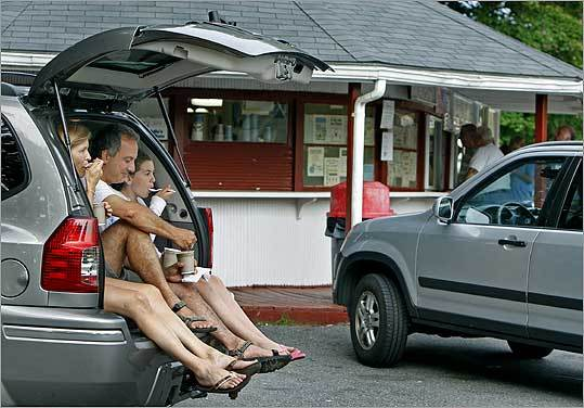 The Quattrini family, mom Suzie (left), dad Vic, and Anna, 11, of Merrimac enjoyed their treats from Hodgie's Ice Cream in Amesbury while sitting in the back of their sport utility vehicle.