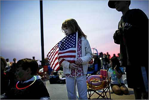 Hannah Finn, 5, of Andover held her flag on the roof of the garage of the Museum of Science in Cambridge before the fireworks show during the Fourth of July celebration in Boston.