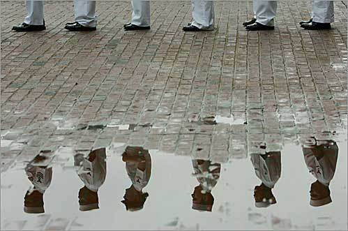 Sailors from the USS Bataan were reflected in a puddle on City Hall Plaza before they marched in Boston's Fourth of July parade.