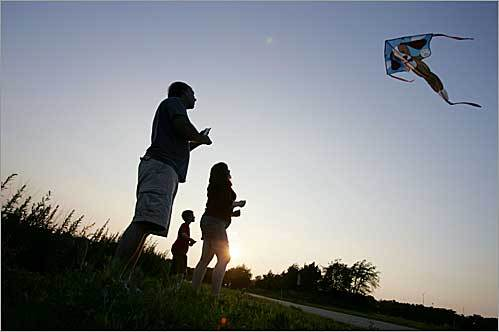 Scott Bergeron (left), Christopher Bergeron, and Jennifer Healy flew their kites at Pope John Paul II Park in Boston as the sun set behind them.