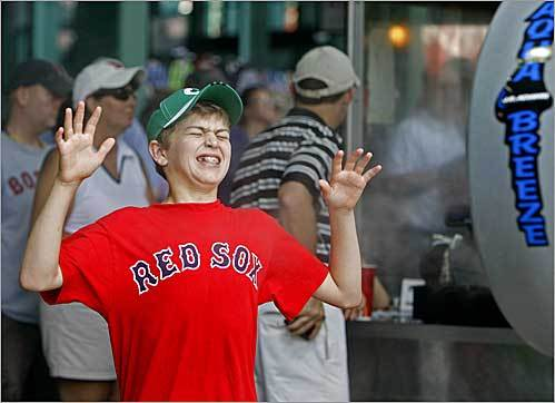 Because of the oppressive heat at Fenway Park, the Red Sox set up some misting machines under the stands where fans could cool off. Mitchell Tuttle, 13, who wore a Red Sox shirt and a Celtics cap despite hailing from Minnesota, took advantage of the cool breezes.