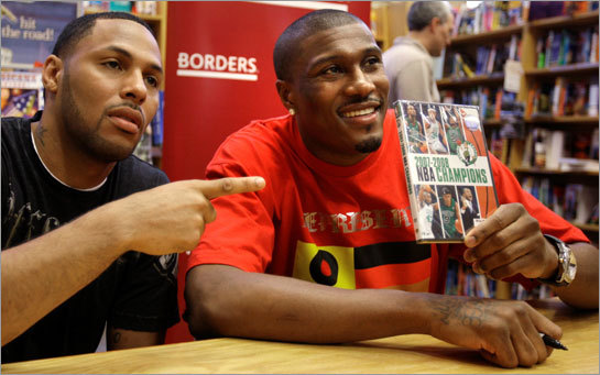 Free agents James Posey, right, poses with Eddie House while signing autographs on a DVD of the Celtics' NBA Championship season.