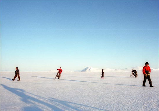 Children play on the frozen waters of a strait that connects to the Bering Strait, beyond the distant mountains.