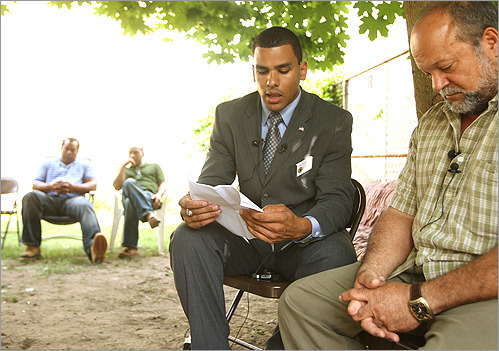 Francisco A. Urena, left, director of the Department of Veterans' Services of Lawrence, read a letter from Alex Jimenez, whose body was found in Iraq, detailing why Jimenez wanted to join the US Army. Jimenez's father, Ramon, listened as Urena spoke.