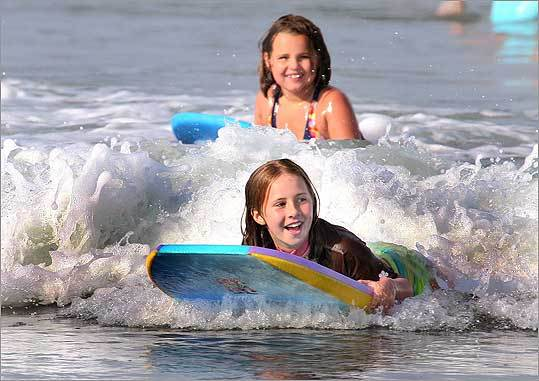 Payten Jackman (front) of Westwood and her friend Madison Kajunski of Weymouth rode their boards in the shallow surf at Nantasket Beach in Hull.