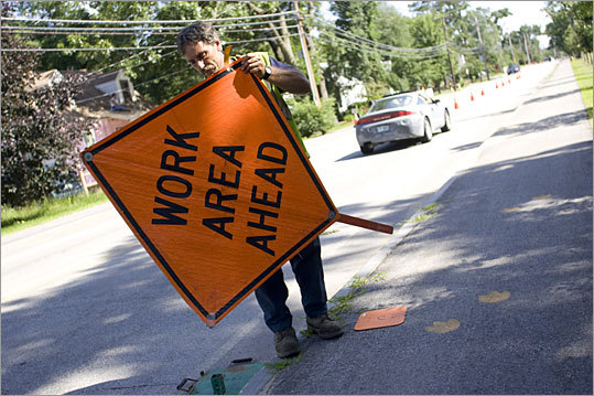 Utility technician Bob Demers removes a sign ahead of a sewer repair site. Concord, N.H., has put some workers on a four-day week.