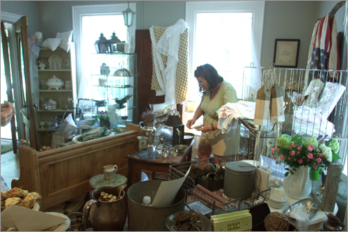 In the house's other room, a customer searches amongst the antiques.