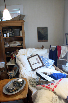 In one of the two rooms downstairs, trinkets, dishes and picture frames are scattered about a couch.