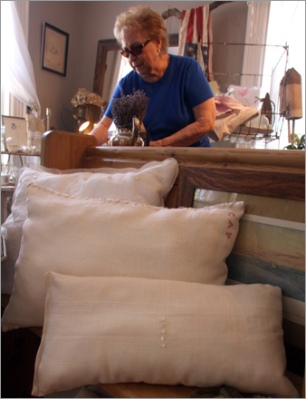 Helen Von Hagen of New York browses behind vintage fabrics and vintage trimmed pillows made locally for Henn House.